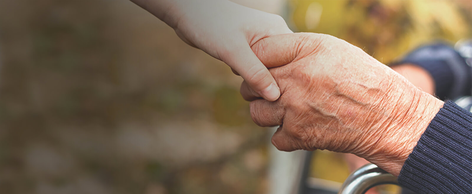 Young person hand reaching down to hold the hand of an elderly person