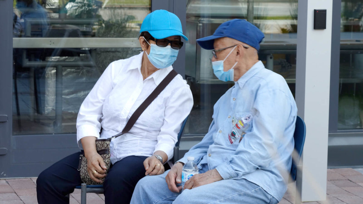 People wearing face masks sitting outdoors